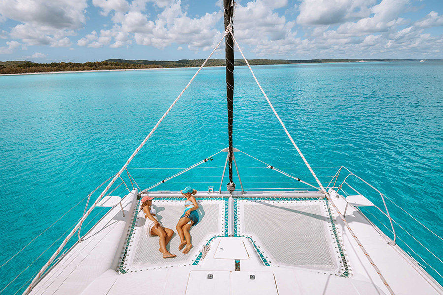 Two girls laying on front of yacht