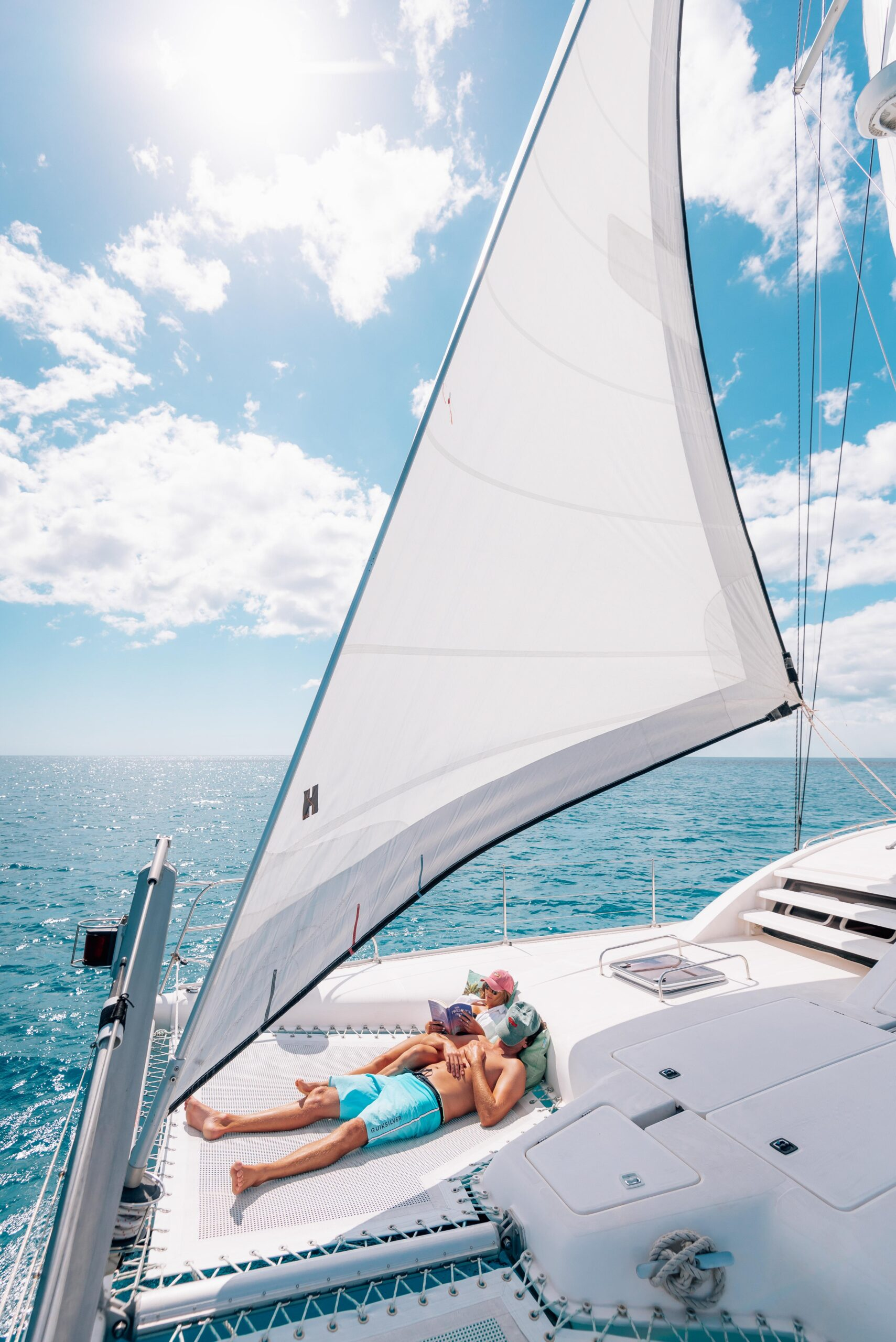 Two people laying on the front nets of a sailing catamaran