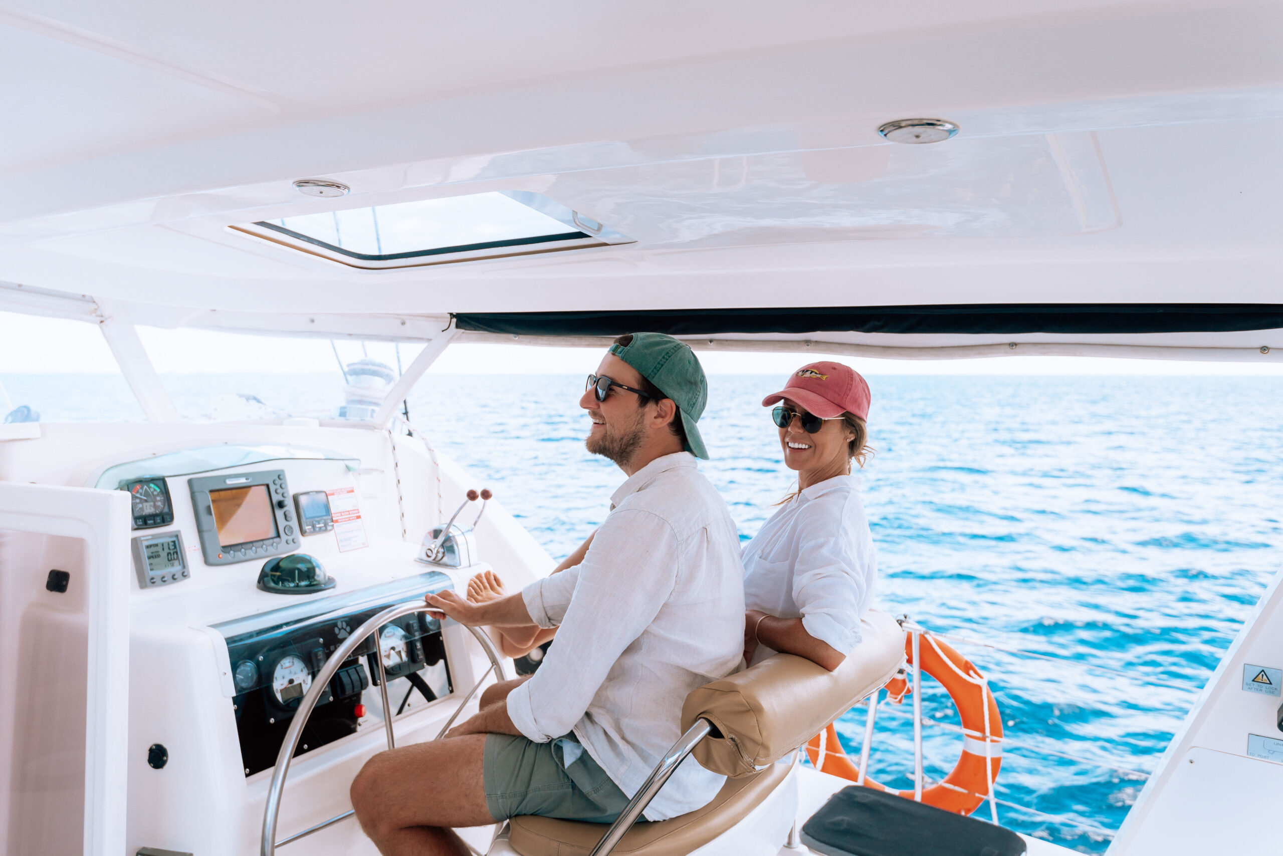 Two people at helm of a yacht charter
